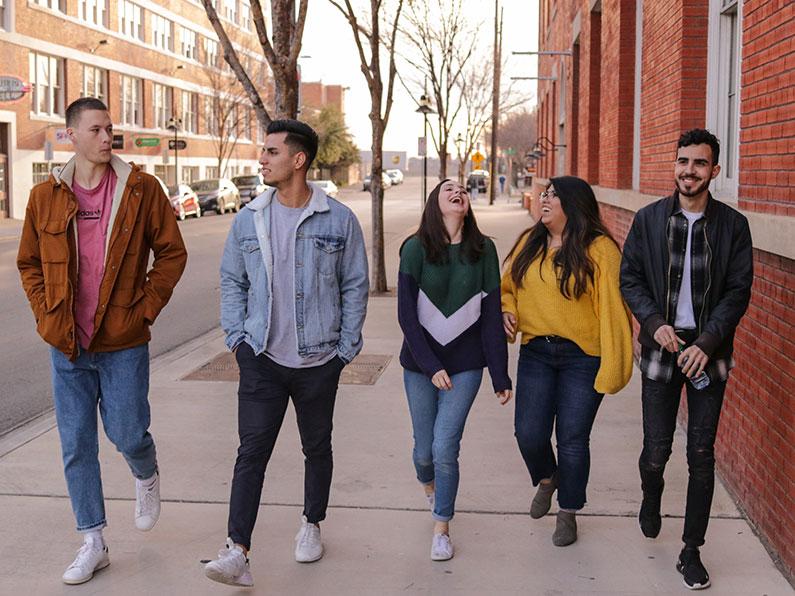 Five high school age people walking
