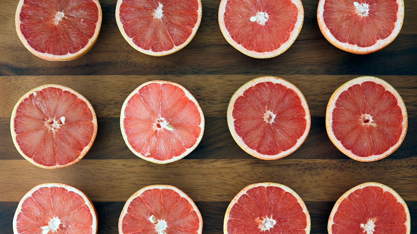 halved grapefruit on cutting board