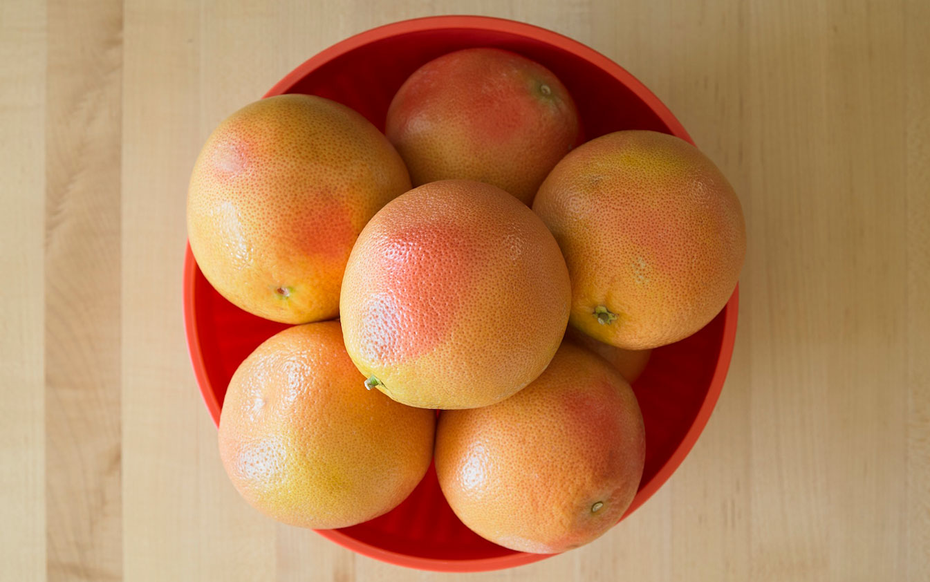 Bowl of grapefruits on a cutting board