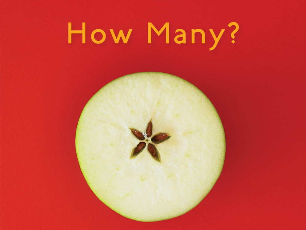 Book cover for How Many? A counting book. An apple is sliced horizontally, revealing a 5-pointed star of seed capsules.